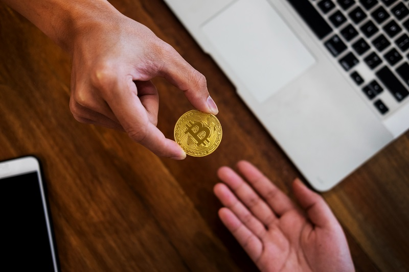hand exchange golden metal Bitcoin crypto currency investment- symbolic block chain financial internet and technology.